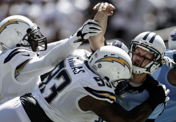 Tennessee Titans quarterback Jake Locker, right, throws as he is hit by San Diego Chargers defensive tackle Cam Thomas, center, and outside linebacker Shaun Phillips during the second quarter of an NFL football game on Sunday, Sept. 16, 2012, in San Diego. (AP Photo/Lenny Ignelzi)